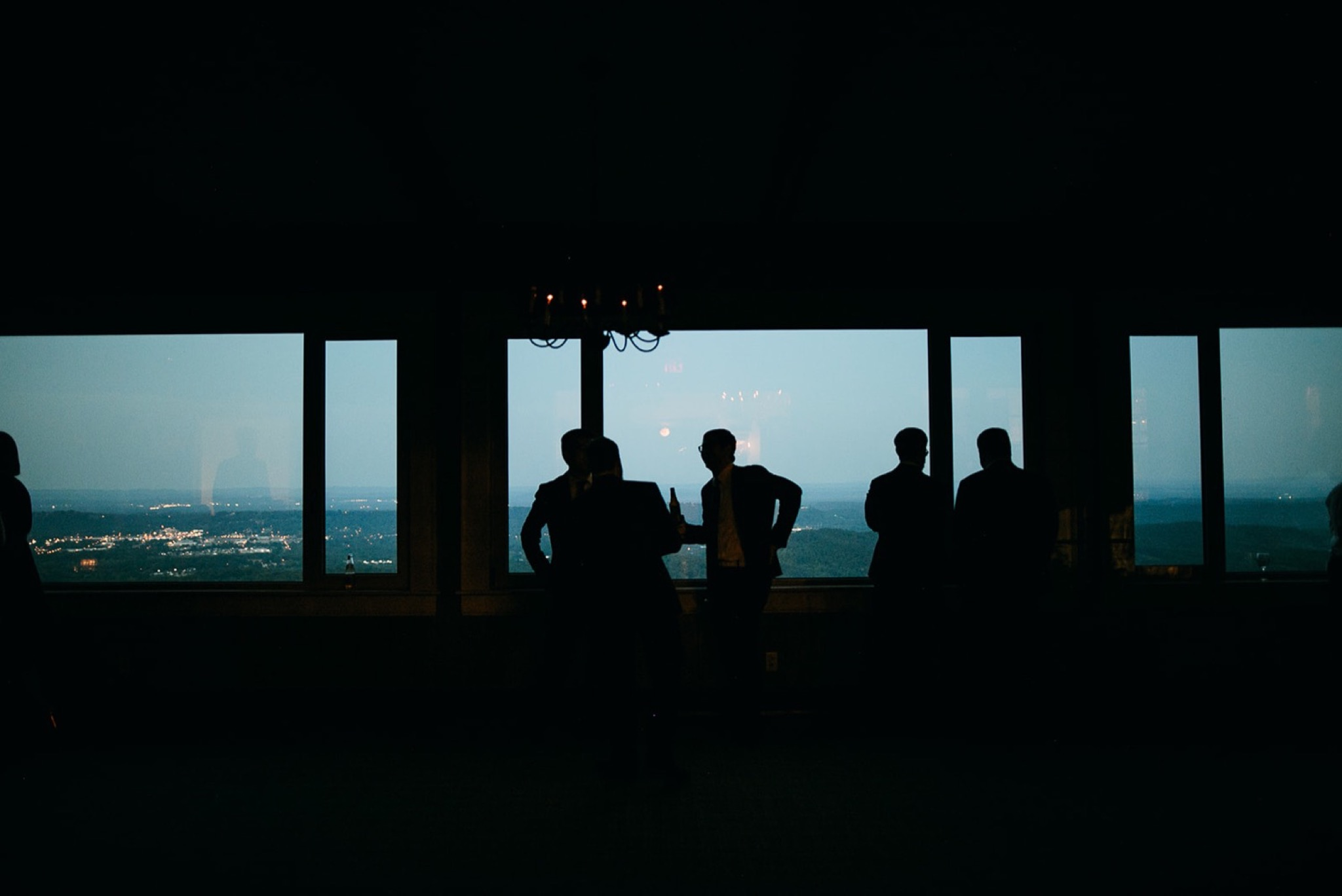 wedding guests silhouettes against large windows overlooking the Chattanooga valley