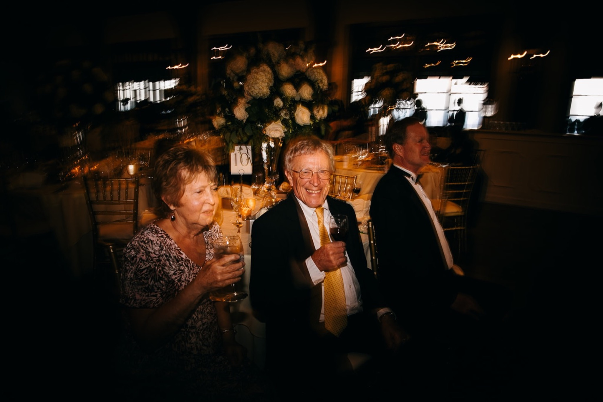 an older couple holds wine glasses and smiles while watching people dance