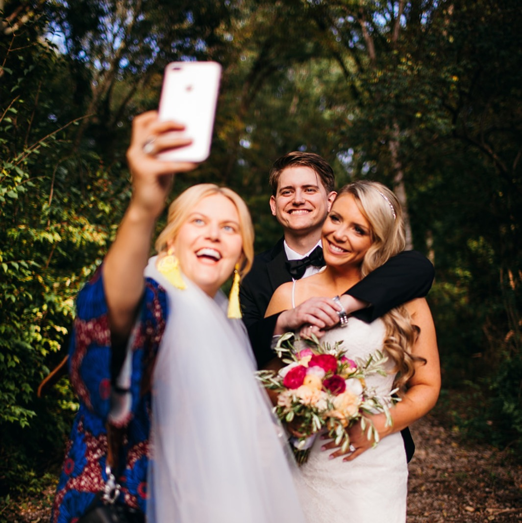 Wedding photographer takes an iPhone selfie with the bride and groom on their wedding day.