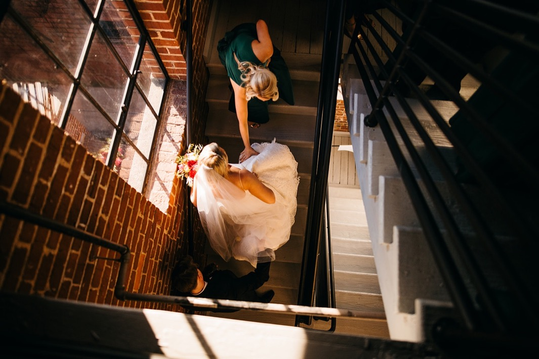 Bride and groom walk up the stairs of their wedding at the Turnbull building.