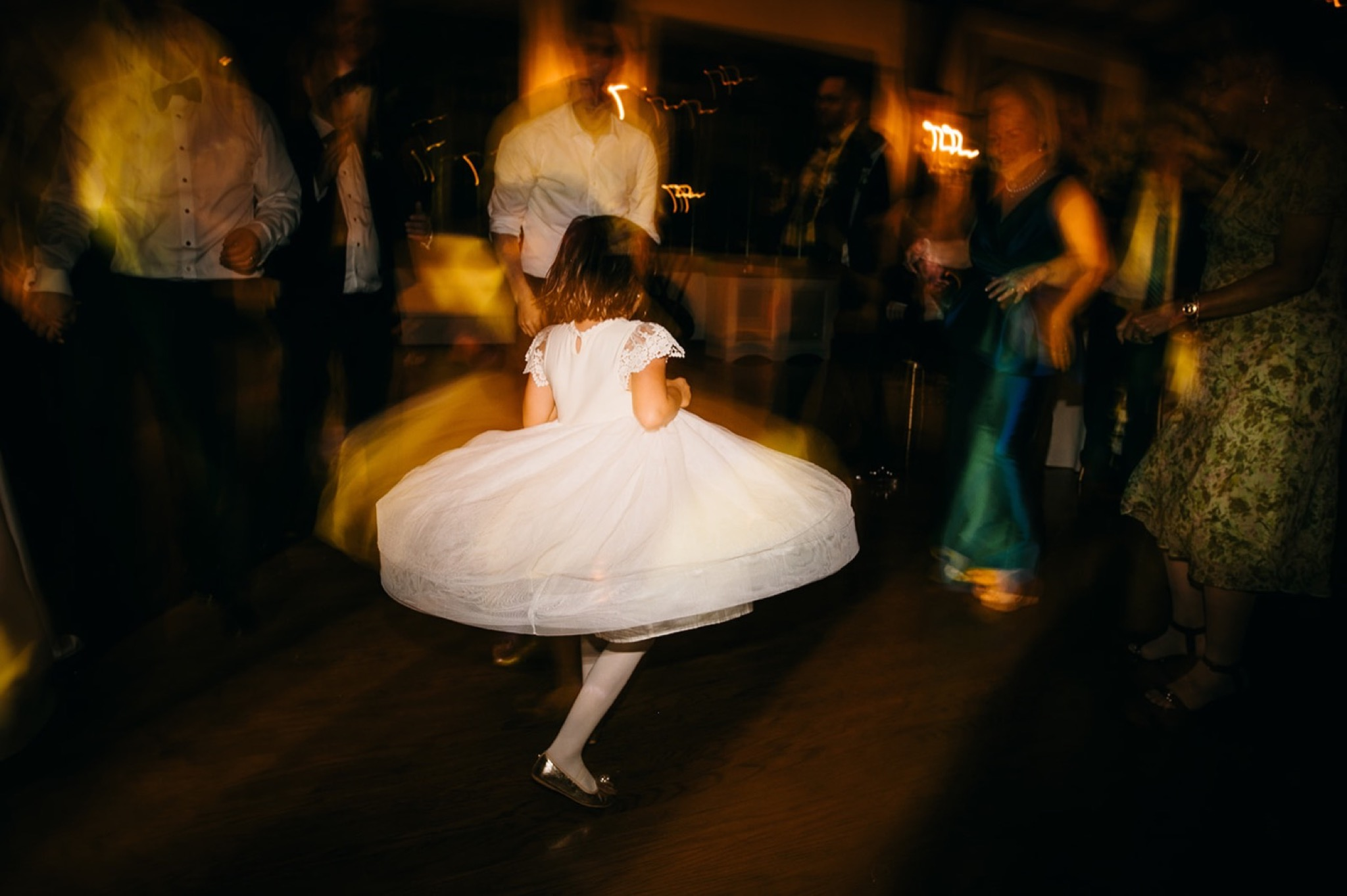 a young girl twirls in a white dress while adults dance around her