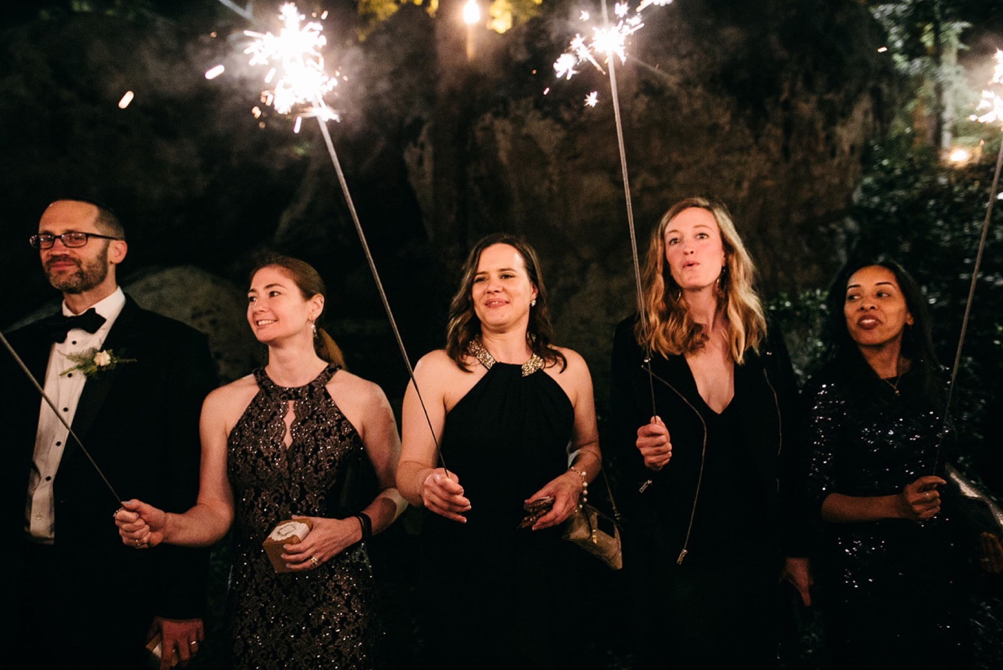wedding guests hold long sparklers and smile