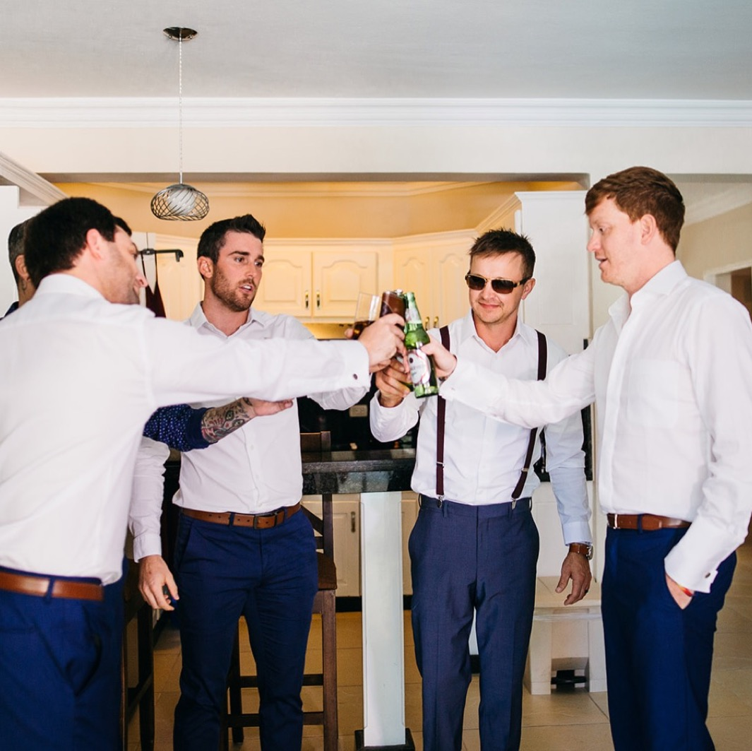 men in blue dress slacks and white shirts clink beer bottles together in a toast