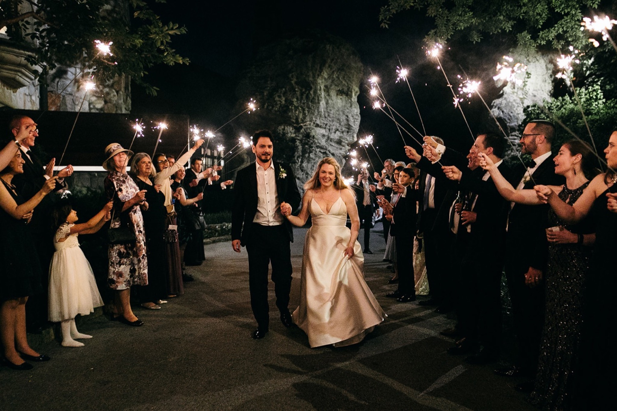 bride and groom hold hands and walk between wedding guests holding sparklers