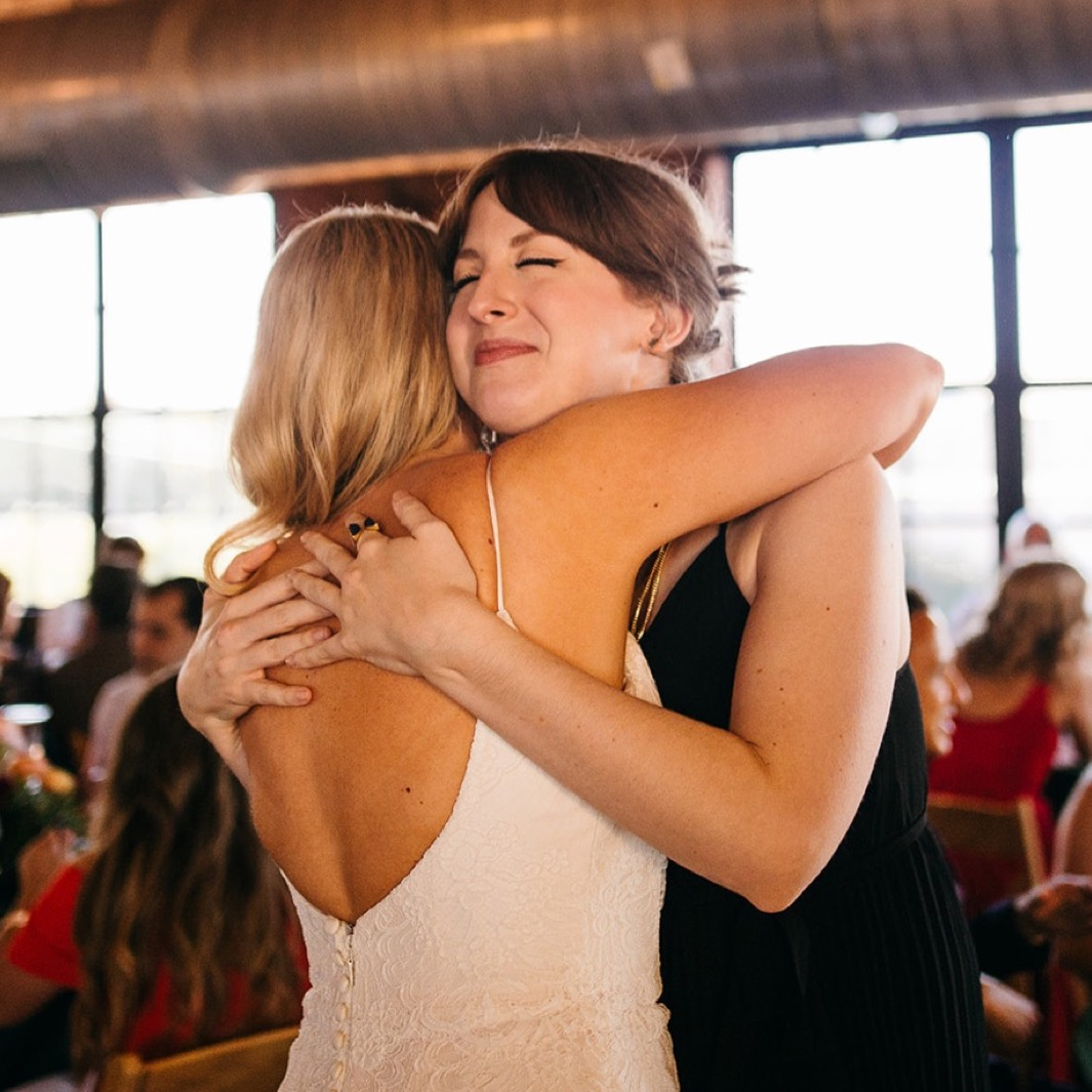 Bride gives a friend a hug during the reception of her wedding at the Turnbull building.