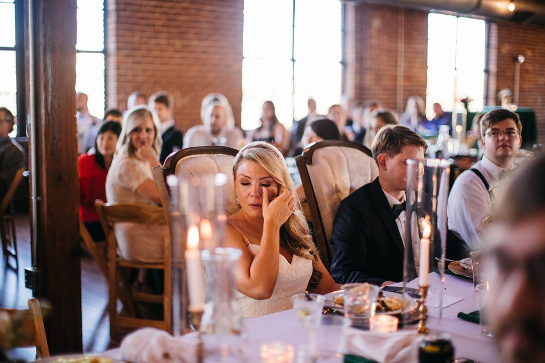 Bride wipes away a tear after her maid of honor's speech.