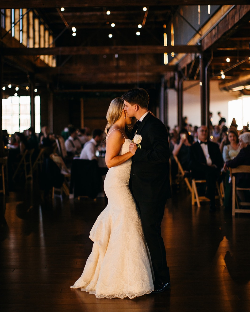 Bride and groom hold eachother close during their first dance at their wedding in the Turnbull building.