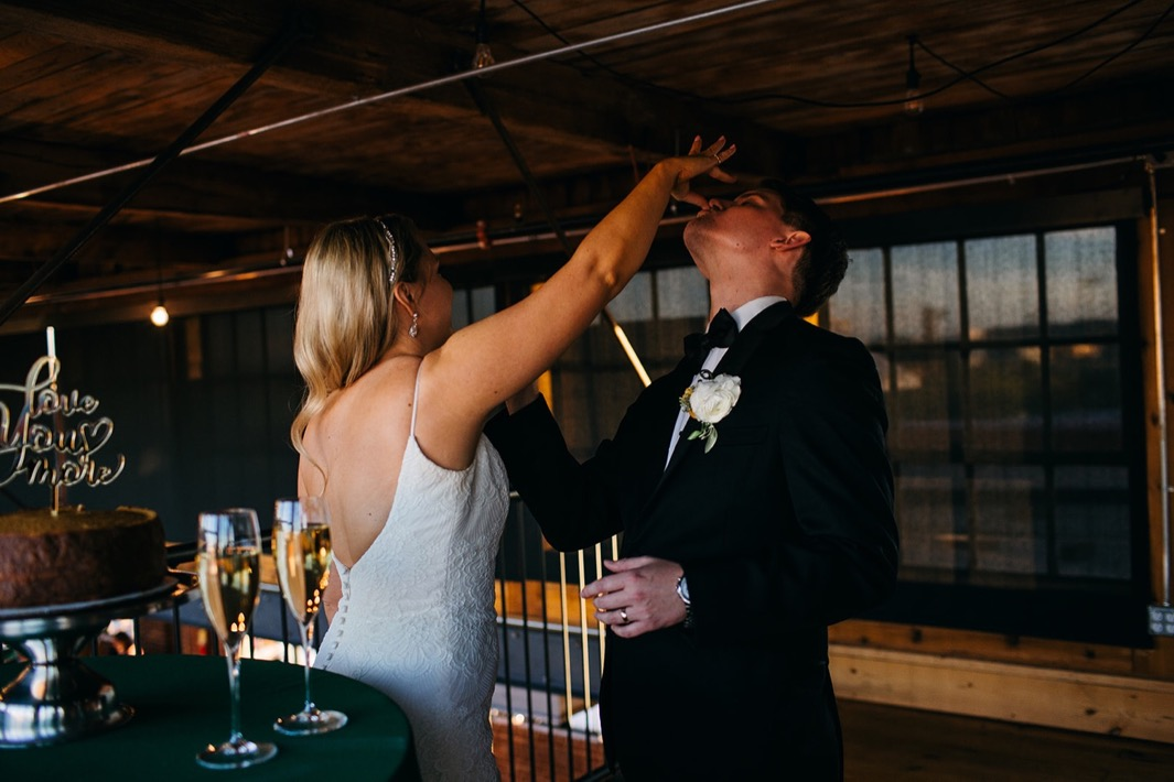 Bride and groom feed each other a piece of their wedding cake during their wedding at the Turnbull building.