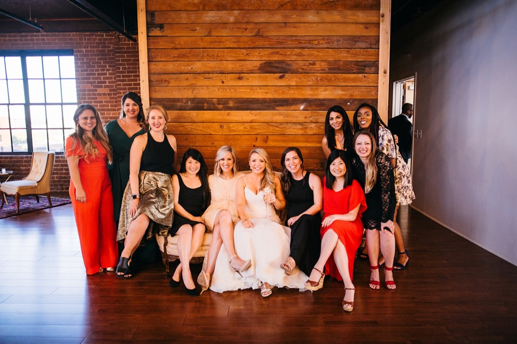 Bride smiles with her friends for a photo at her wedding in the Turnbull building.