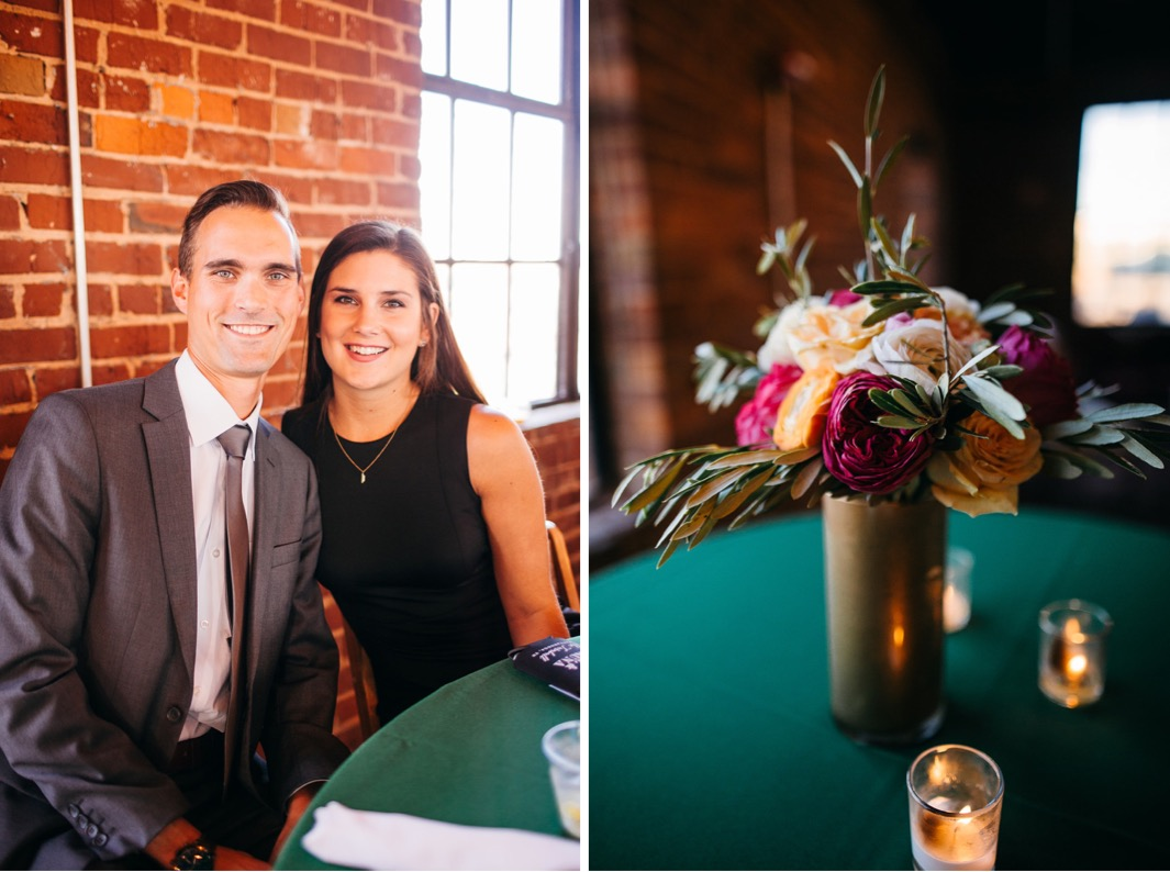 Wedding guest couple sit at a table and smile for a photo.