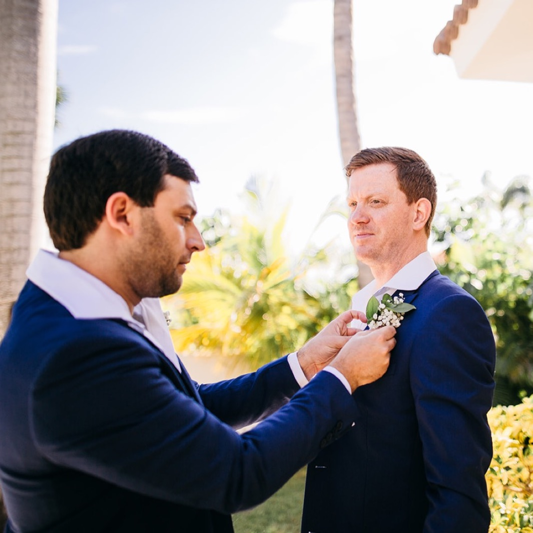 man pins white boutonniere on groom's blue sport coat