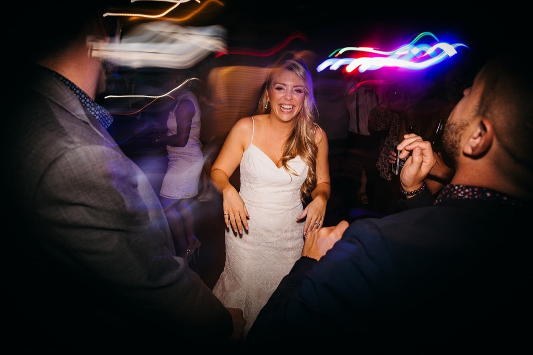 Bride laughs on the dance floor of her wedding in the Turnbull building.