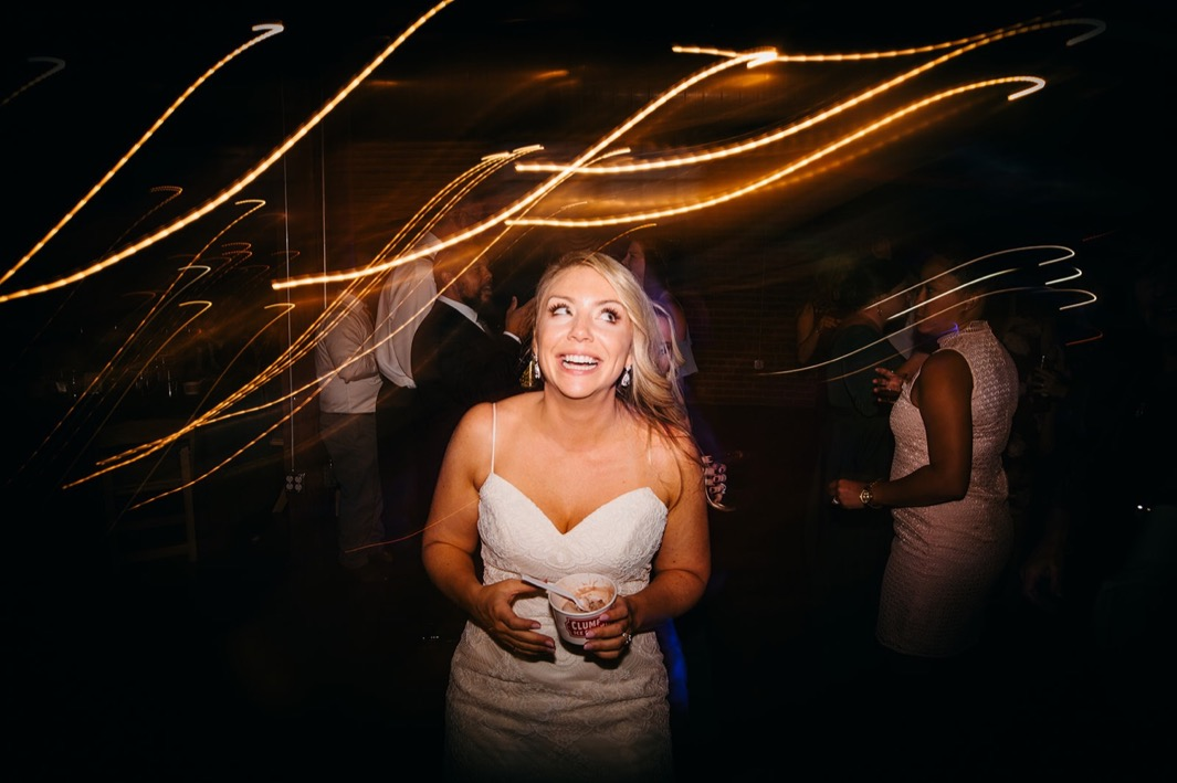 Bride holds her ice cream and smiles during her wedding at the Turnbull building.