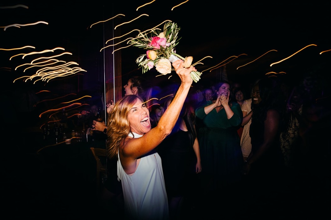 Wedding guest holds the bouquet up after she catches it from the bride.