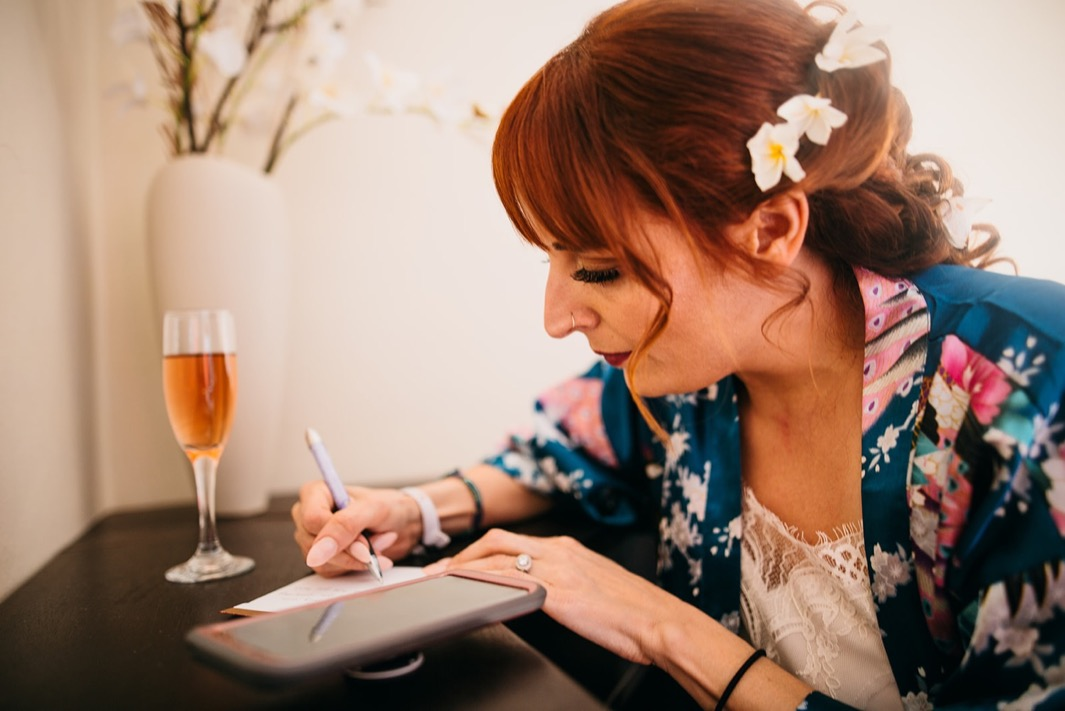 woman in colorful bathrobe with white flowers in her hair writes a letter at a desk