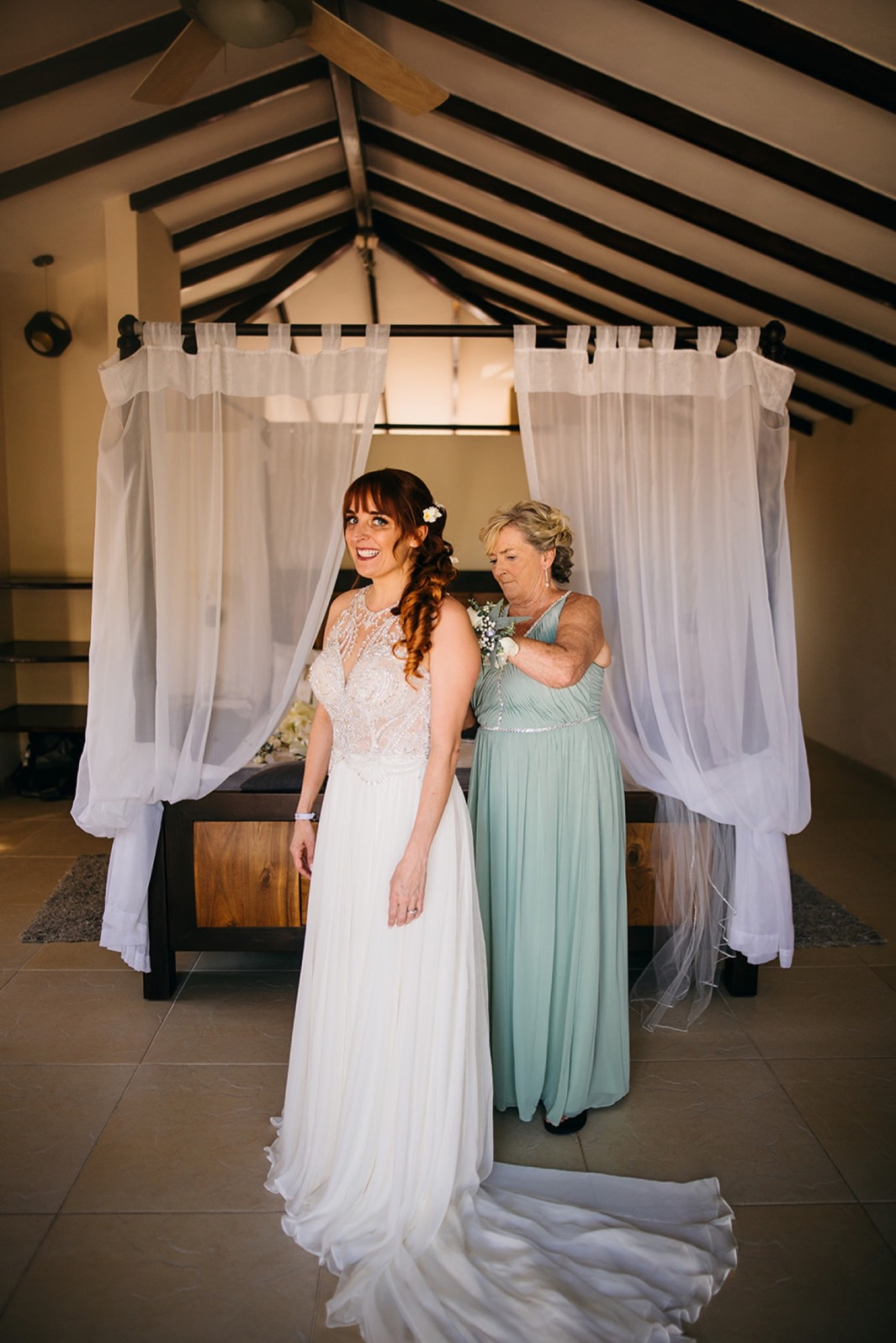 brides mother fastens the back of her wedding gown in front of white-curtained canopy bed