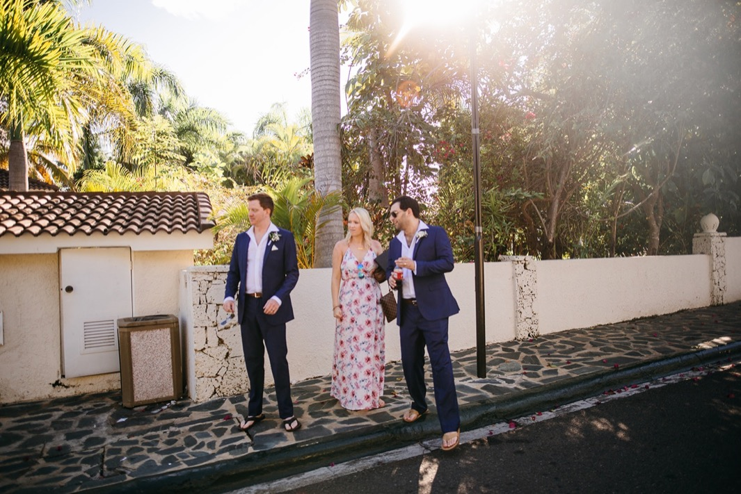 two men and a woman stand on stone sidewalk under palm tree