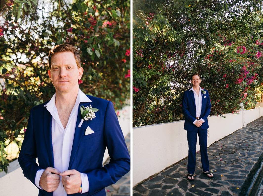 groom in blue suit and white shirt and flip flops stands on stone sidewalk under red flowering shrubs