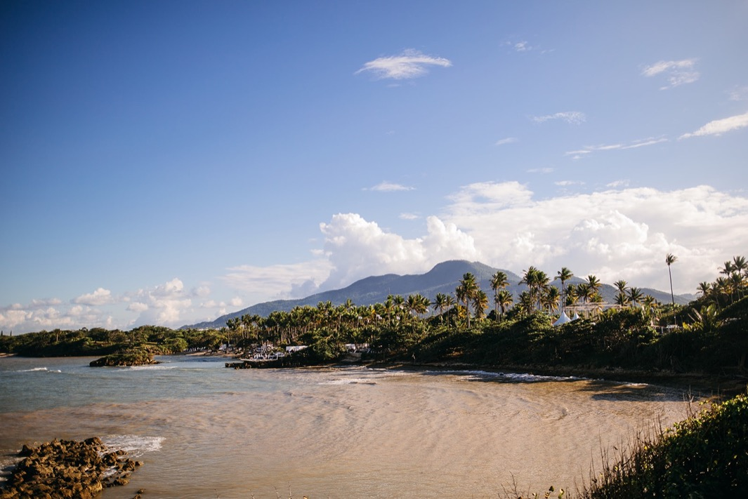 private beach inlet surrounded by lush greenery with mountains in the background