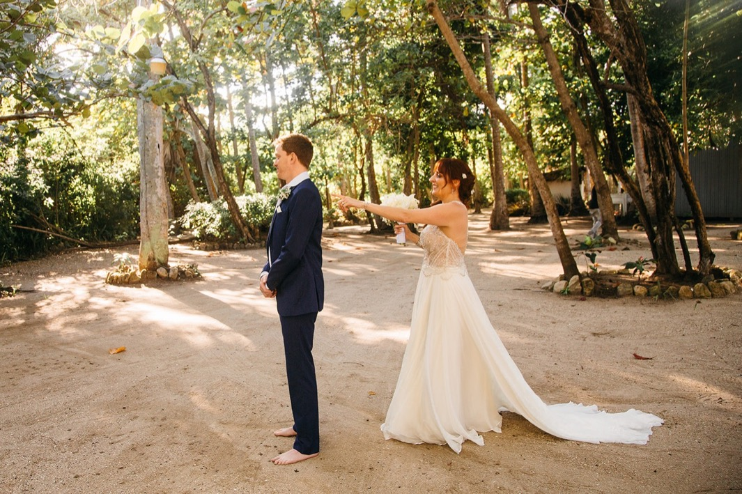 bride in white gown taps grooms shoulder as he waits barefoot in the sand for their first look