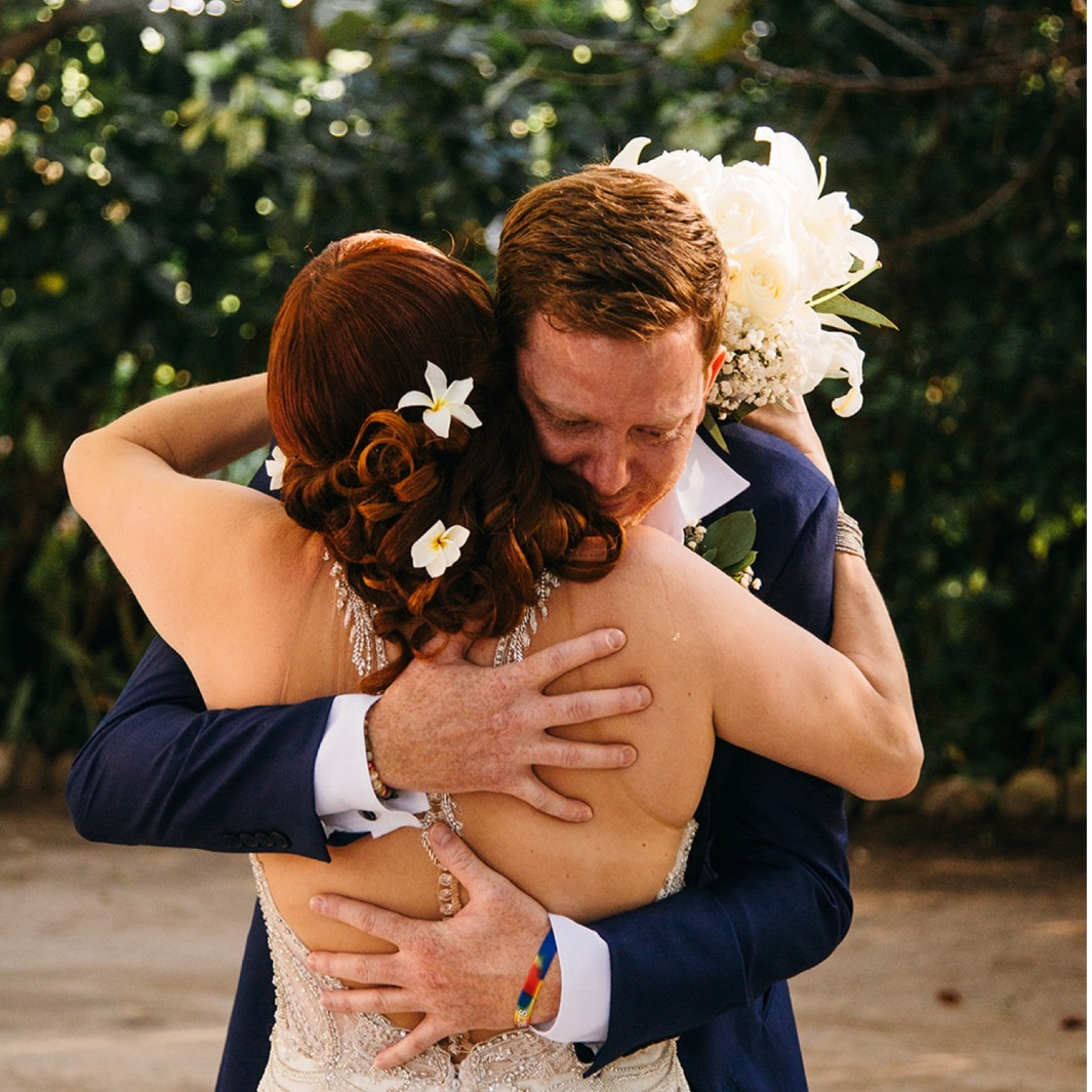 groom hugs bride who has white flowers in her hair