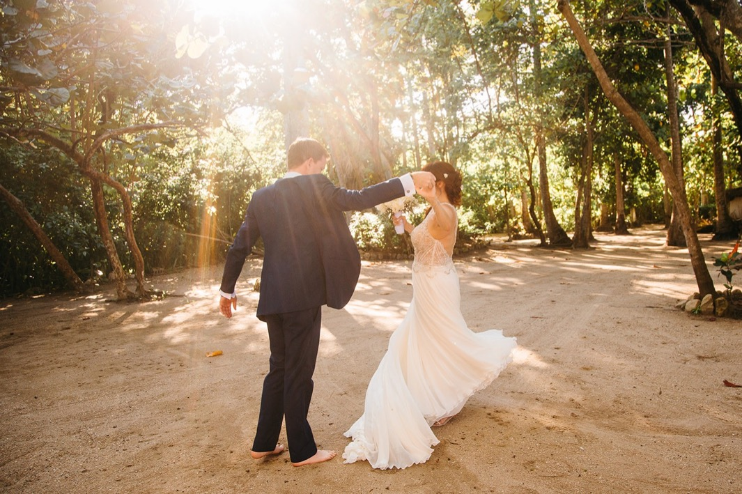 barefoot groom twirls barefoot bride under lush green canopy as they elope in the Dominican Republic