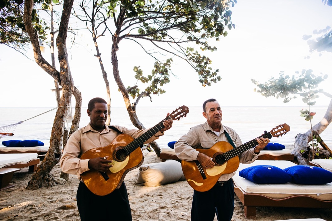 two men play guitars under trees on the beach