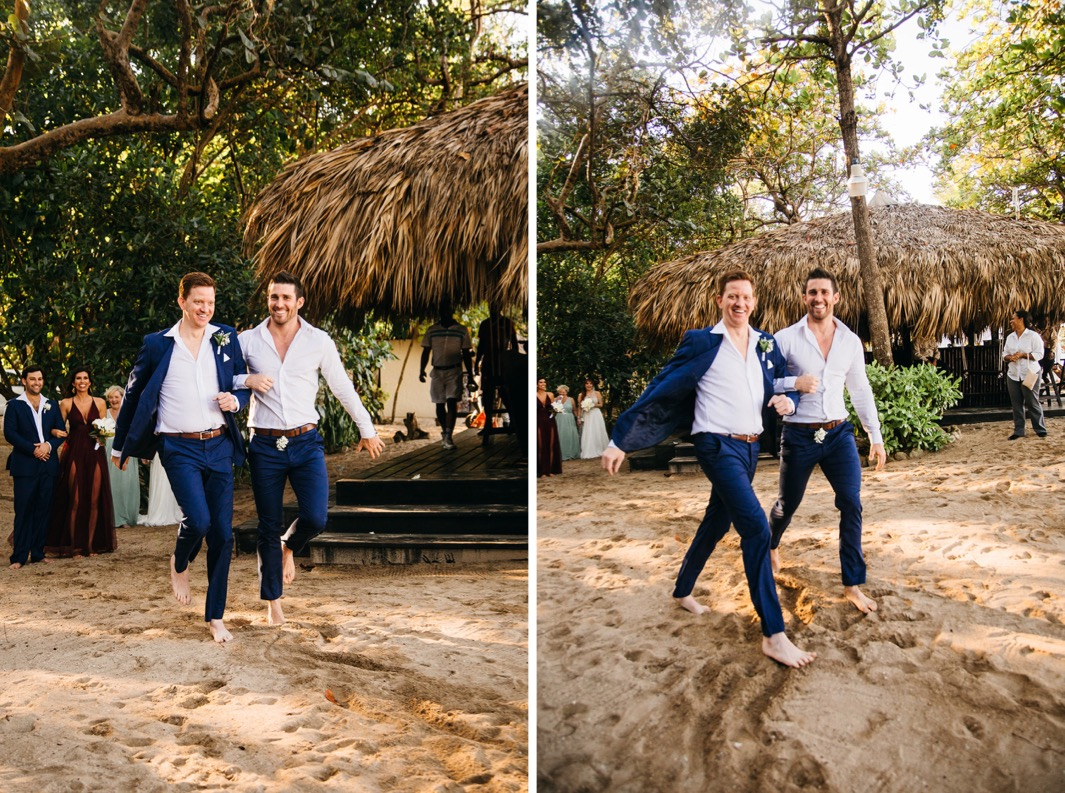 groom and friend in blue suit pants skip barefoot through the sand to ceremony site