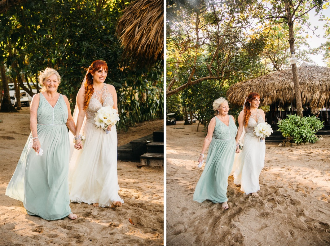 bride in flowing gown holds hands with her mother in seafoam green dress as they walk barefoot in the sand down the aisle
