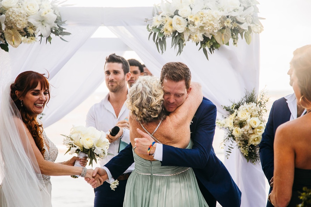 mother of bride hugs groom at the front of the aisle with flower-covered wedding arch behind them