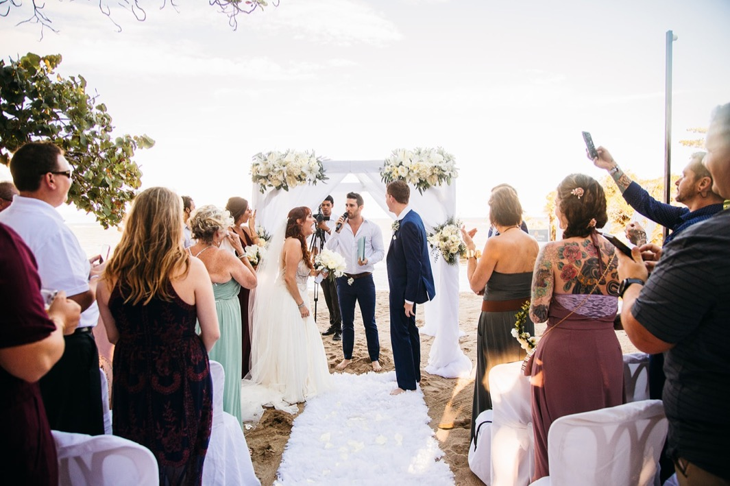 wedding guests stand as officiant welcomes bride and groom and others to ceremony site on Dominican Republic beach