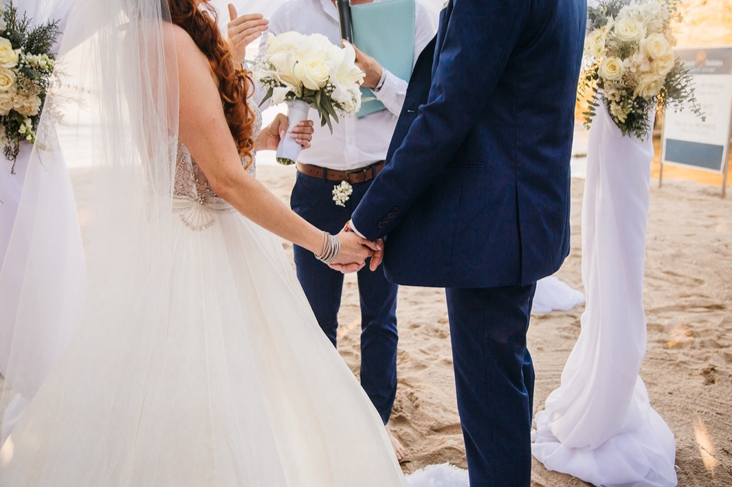 bride and groom hold hands during their ceremony as they elope in the Dominican Republic with close friends and family