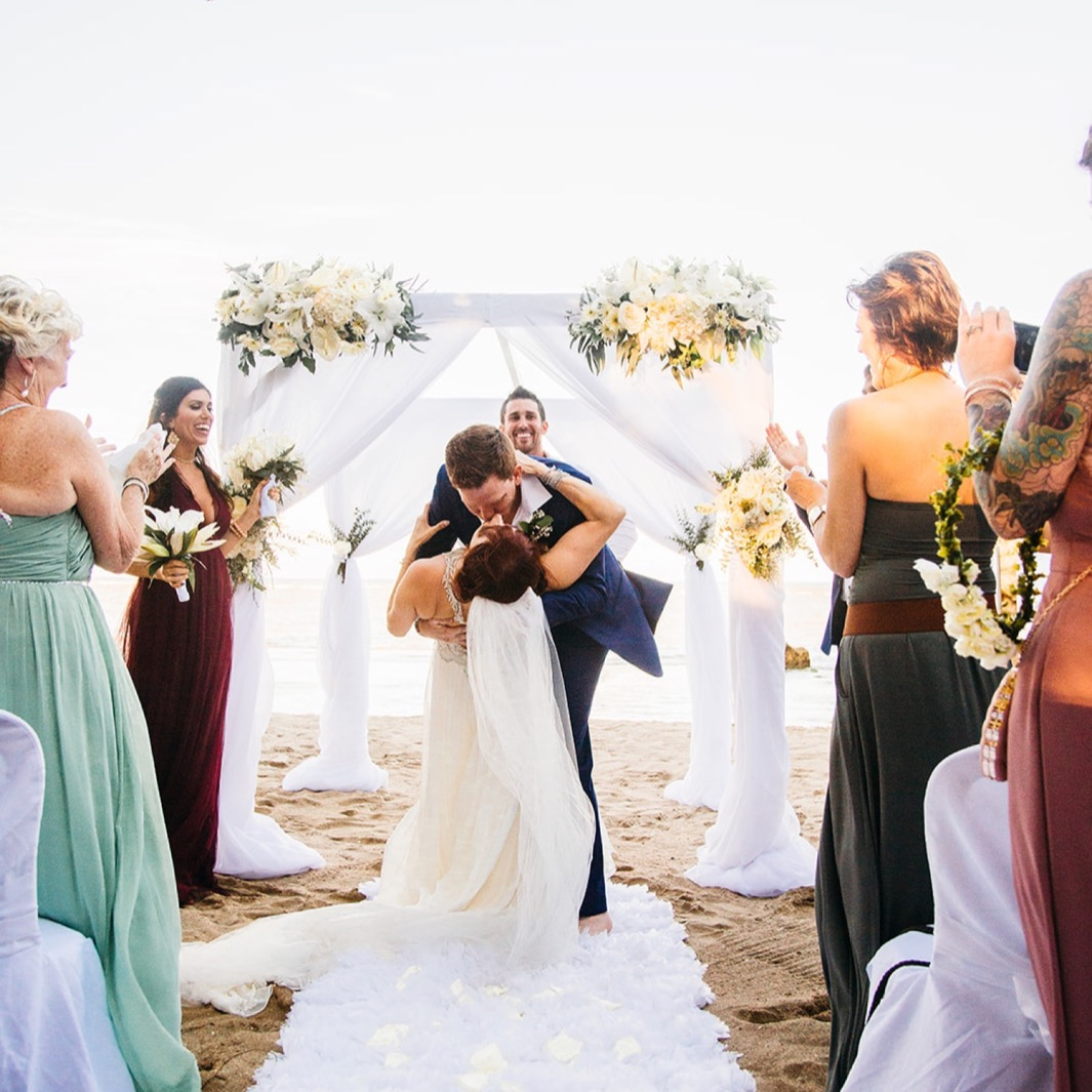 groom dips bride during kiss as they elope in the Dominican Republic with friends standing and cheering during beach ceremony