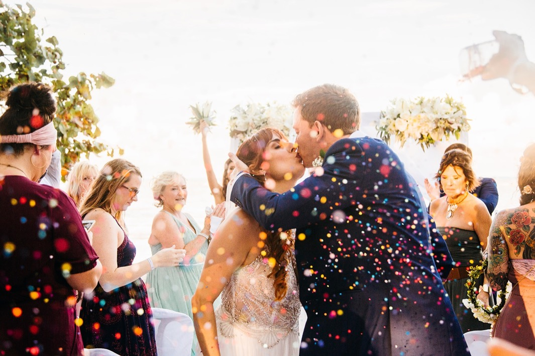 bride and groom kiss through confetti after they elope in the Dominican Republic on the beach with friends and family