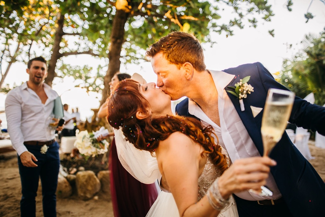 bride and groom kiss with confetti in their hair and toast with champagne after they elope in the Dominican Republic