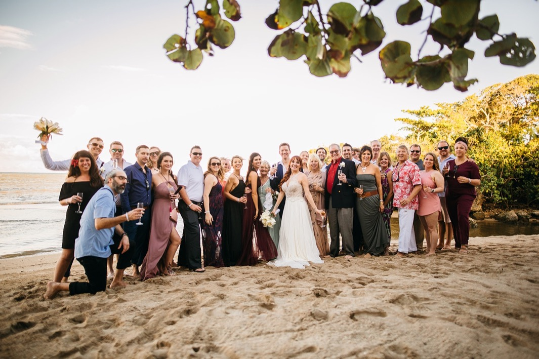 bride and groom stand on the beach in the Dominican Republic with family and friends following their elopement ceremony