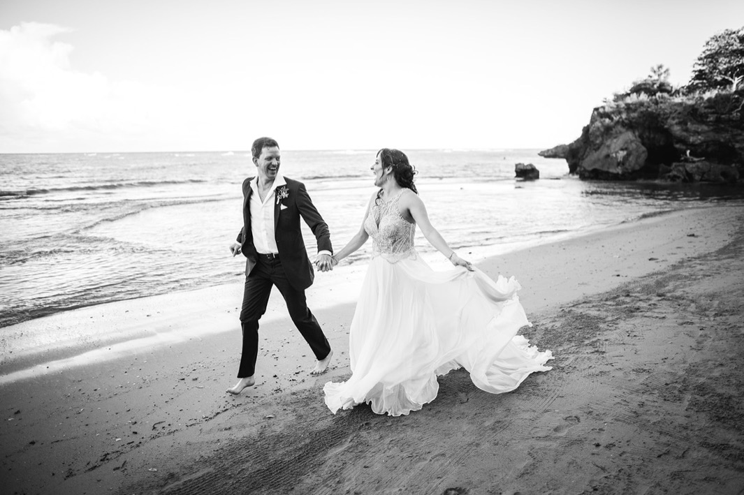 bride in sequin bodice wedding gown and groom in blue suit walk barefoot on beach as they elope in the Dominican Republic