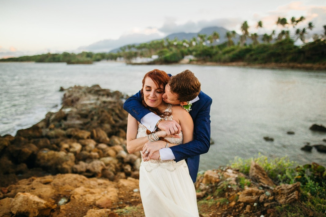 groom in blue suit hugs bride in white gown with beach, trees, and mountains of the Dominican Republic behind them