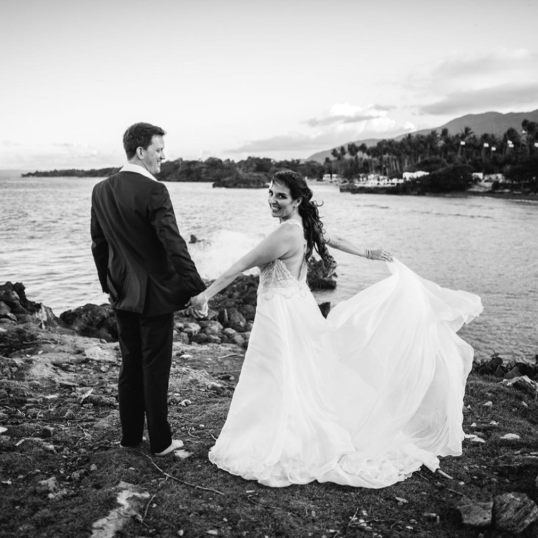 bride holds her dress train and grooms hand on an overlook of the ocean