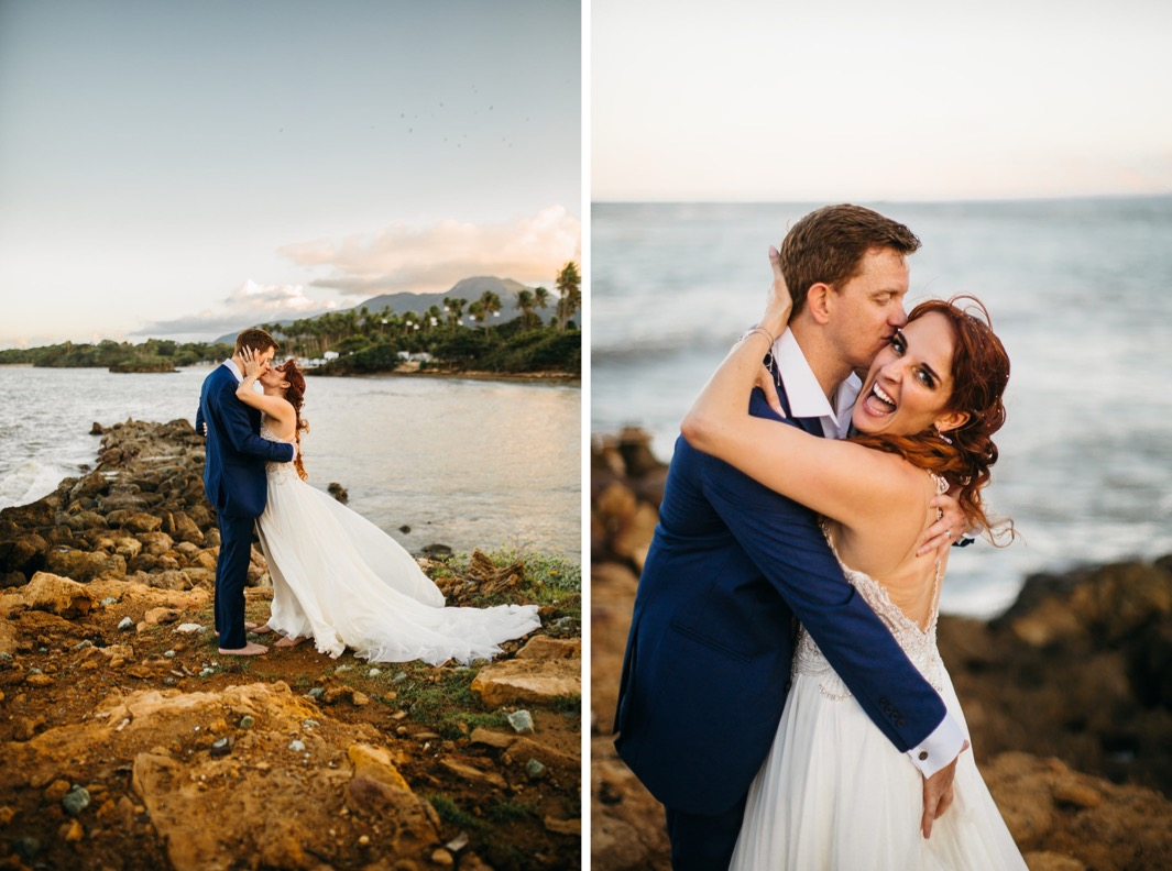 groom in blue suit kisses bride in white gown with beach, trees, and mountains of the Dominican Republic behind them