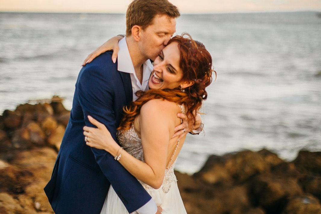 groom kisses bride's temple as she laughs with ocean behind them