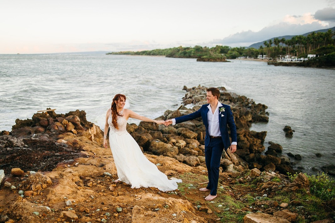 bride and groom hold hands on rocky beach overlooking water in the Dominican Republic