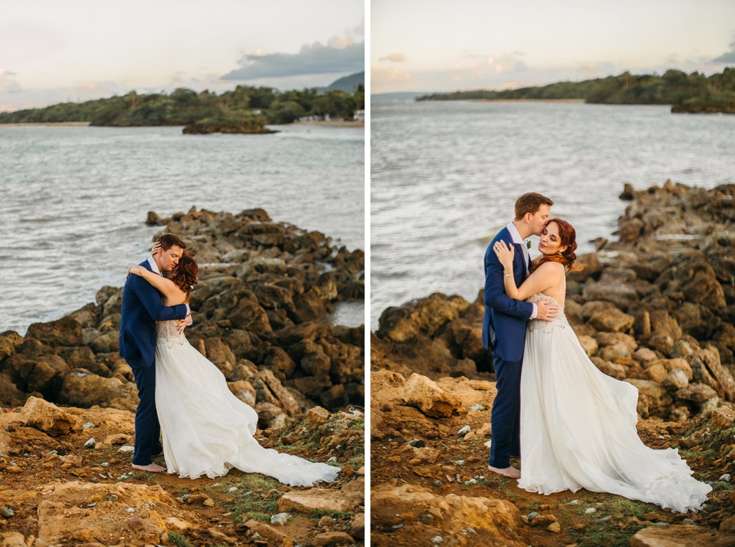 bride and groom snuggle closely on a rocky beach in the Dominican Republic