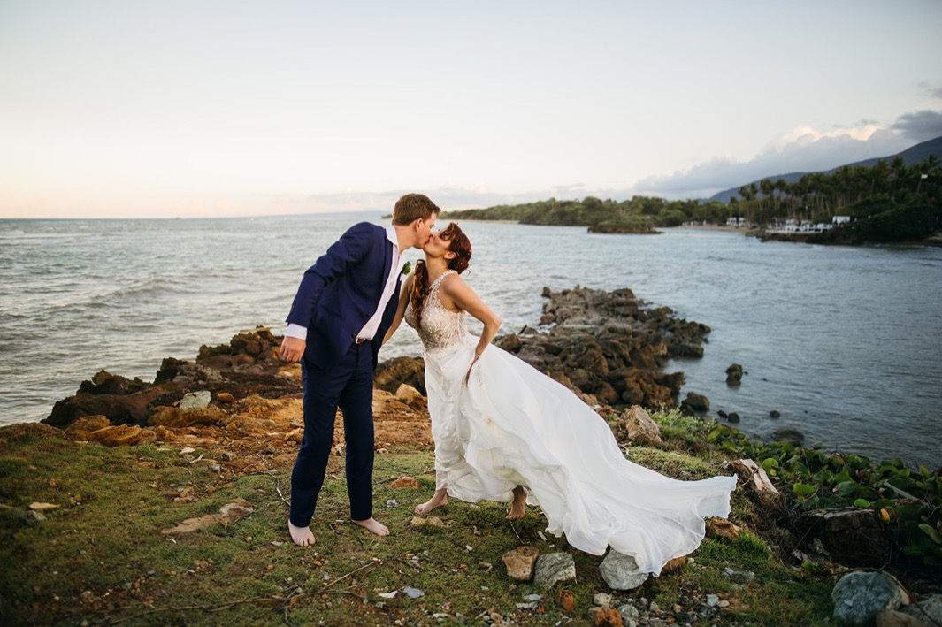 barefoot bride and groom kiss at dusk overlooking water after they elope in the Dominican Republic