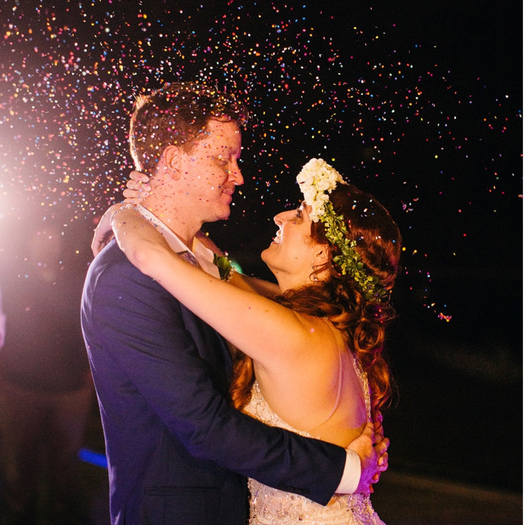 bride wearing flower crown smiles and dance with groom as guests shower them with confetti