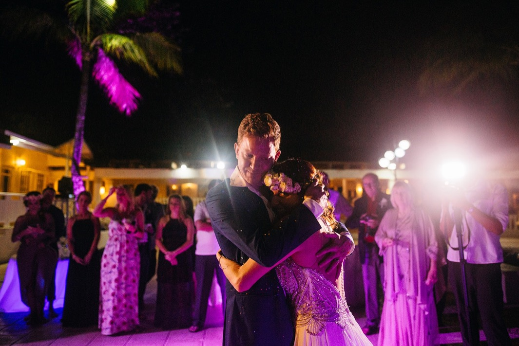 bride and groom hug each other tightly during first dance while wedding guests watch in the background