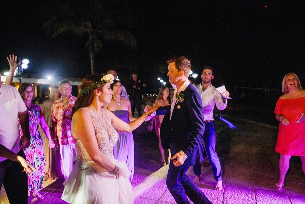 bride and groom dance with wedding guests in the dark night after they elope in the Dominican Republic