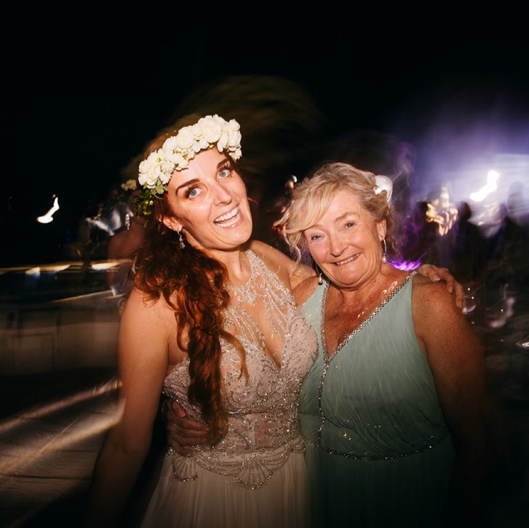 bride in flower crown and sequined wedding dress hugs her mother on the dance floor