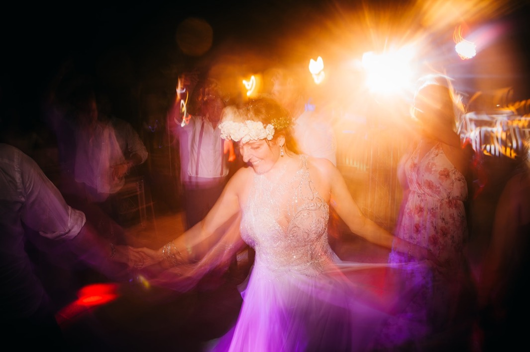 bride in flower crown and sequined wedding gown dances with wedding guests at her Dominican Republic elopement reception