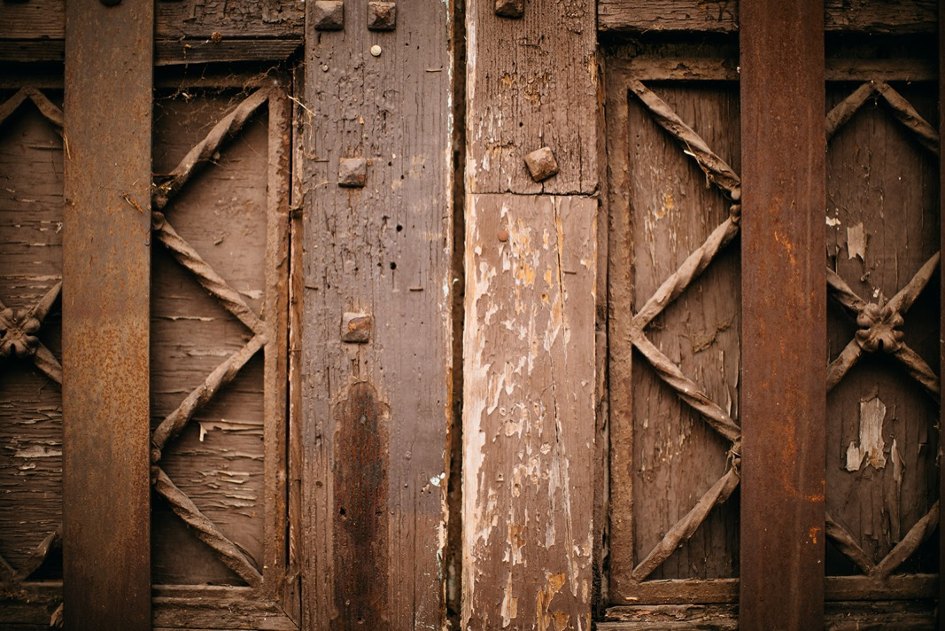 antique wooden doors with peeling paint and metal detailing